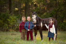 posed children standing with pony
