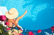 Woman relaxing at the swimming pool and testing water