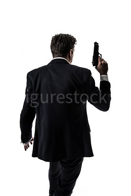 A mystery man in a suit, walking with a gun raised, in semi-silhouette – shot from eye level.