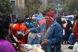 A yatiri or shaman blesses miniatures with incense, Alasitas festival, La Paz, Bolivia
