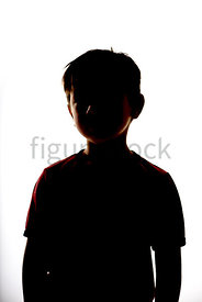 A Figurestock image of the silhouette of a boy standing in a t-shirt - shot from mid level.