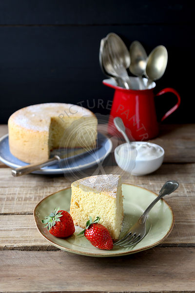 Slice of sponge cake with cream and fresh strawberry on a plate