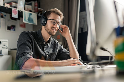 Smiling young man wearing headphones working on computer at desk at home