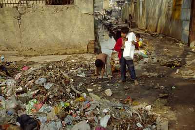 India - New Delhi - A boy uses a polystyrene pack as a drum as he and his friend scavenge for rubbish