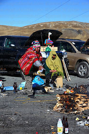 Aymara shaman or yatiri pours alcohol on burning offering (called a k'oa) to Pachamama, La Cumbre, Cordillera Real, Bolivia