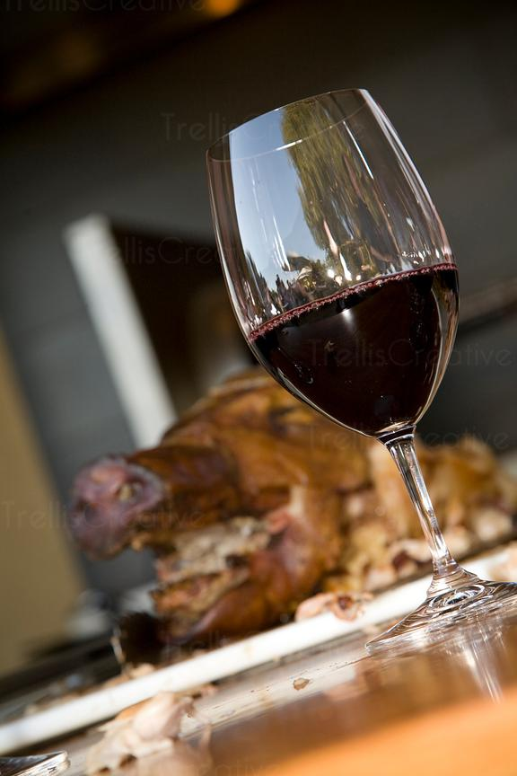 A glass of red wine served with roast pork