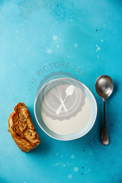 Vichyssoise cold cream soup in bowl with bread on blue background copy space
