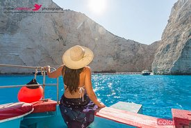 Woman ion yacht looking at famous Navagio beach, Greece
