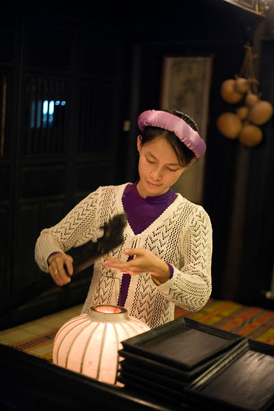A maid lights a lantern