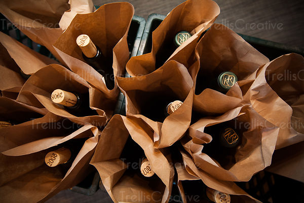 Many wine bottles in brown paper bags at blind wine tasting