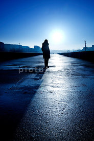An atmospheric image of the silhouette of a mystery woman, walking towards the camera, on a on a housing estate.