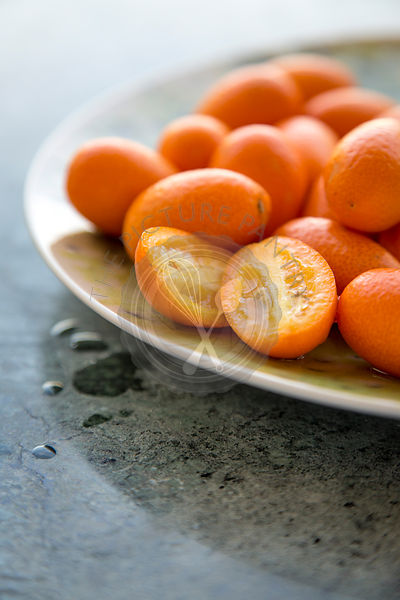 group of kumquats on a green plate on a green marble surface
