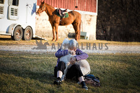 Elderly woman hugs a dog in front of barn with horse in background.