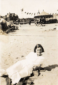 NOT FOR MISERY MEMOIR USAGE - An old family photograph of a woman laying on an seaside beach.