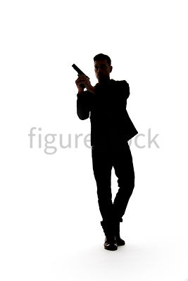 A Figurestock image of a man, in silhouette, walking with a gun – shot from low level.