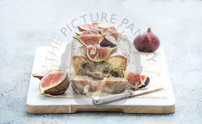 Loaf cake with figs, almond and white chocolate on wooden serving board over grunge background