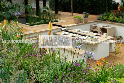 Jardin contemporain en contre-bas. Meuble de jardin : table et banc. Terrasse. Barbecue. Designer : Thomas Hoblyn Design Agency. Hampton Court. Angleterre