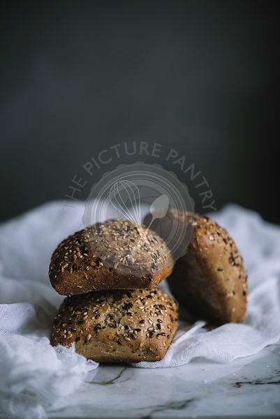 Freshly baked seeded bread rolls in a rustic kitchen