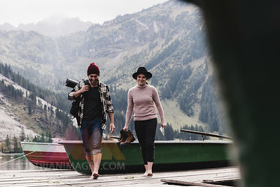 Austria, Tyrol, Alps, couple walking on jetty at mountain lake