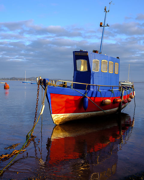Boat moored on the shoreline of the calm Exe Estuary, Exmouth, Devon, UK