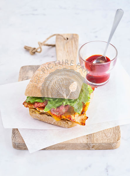 Chicken and bacon burger served on wood board, vertical shot