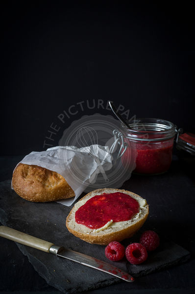 Bread rolls with butter and jam on dark board and background with bread roll in paperback and open jam jarr in background