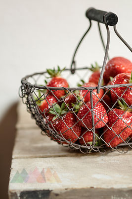 Basket of Strawberries on wooden table, close up