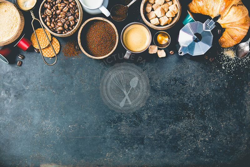Coffee composition on dark background. Coffee espresso in dark cups, coffee beant, ground coffee, brown sugar, milk, croissants, capsules. Food frame concept. Flat lay