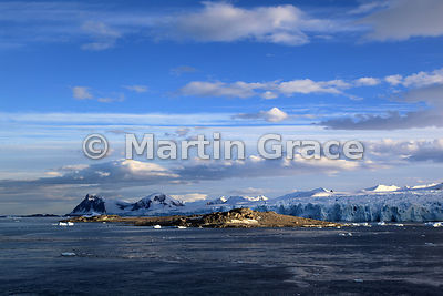 Approaching rocky Stonington Island in Marguerite Bay, West Graham Land, Antarctica, with evening light on clouds against blu...