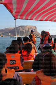 Tourists taking boat trip around port , El Morro headland in background, Arica, Region XV, Chile