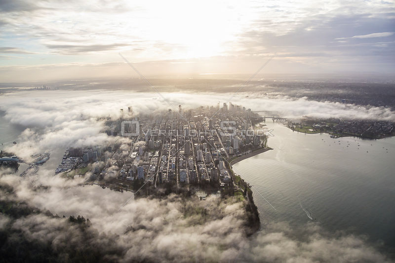 Downtown Vancouver covered by fog and clouds during a morning sunrise.