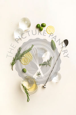 Overhead layout of minimal cocktail ingredients including large ice spheres, lemon wheels, herbs and olives on pale yellow su...