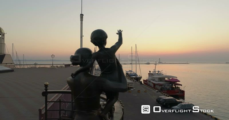 Drone flies at low level past the statue of the seafarers at the Odessa cruise terminal in Ukraine. The sun is rising behind....