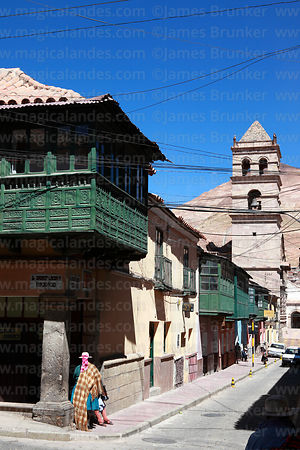 Indigenous lady in colonial street, San Francisco church tower and Cerro Rico, Potosí, Bolivia