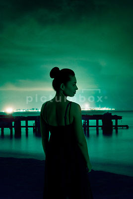 An atmospheric image of a woman in a dress, looking out to sea, on a tropical beach, at night.