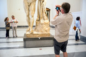 A man takes a photograph of a statue in the National Archaeological Museum in Naples