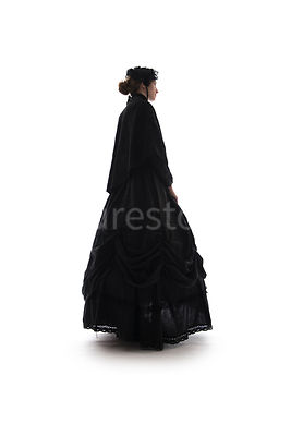 A Victorian woman, in a cape and hat, in semi-silhouette – shot from low level.