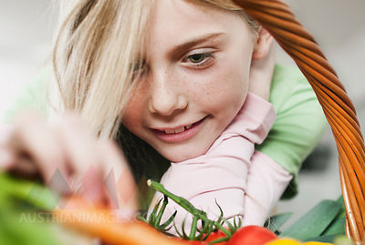 Germany, Cologne, Girl looking at vegetable, close up