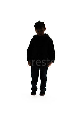A silhouette of a sad boy standing in a coat - shot from mid level.