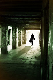 An atmospheric image of a mystery woman with a large bag walking down  a narrow underpass, in Venice, Italy.