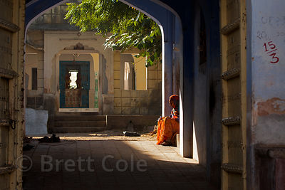 A woman relaxes in the sun drenched entranceway to her house in Pushkar, Rajasthan, India