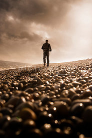 An atmospheric image of a lone mystery man running along a shingle beach in Suffolk, England.