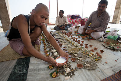 Men perform elaborate prayer rituals to honor deceased relatives, Assi Ghat, Varanasi, India