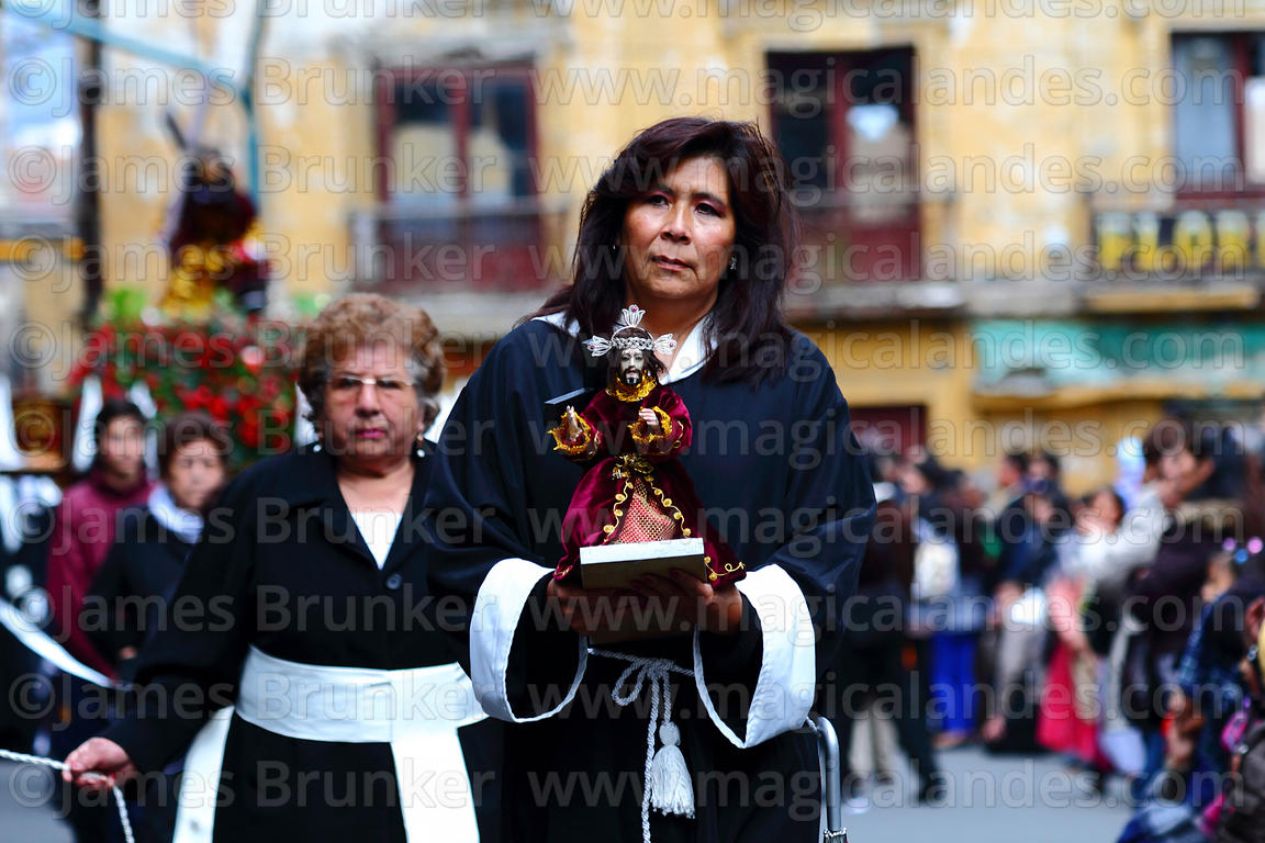 A female member of the brotherhood of Señor de las Caidas / The Fallen Christ carries a small statue during Good Friday proce...