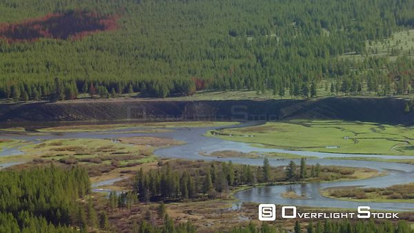 The Madison River winds through a wide valley with scars from a recent forest fire, near Yellowstone National Park