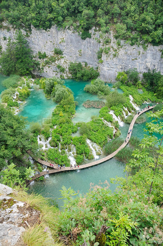 Overview of tourists walking on boardwalk below Velike kaskade waterfalls, with limestone cliffs in the background, Plitvice ...