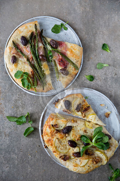 Duo of Pizza, White base pizza, parma ham, asparagus, and olives, watercress garnish.White base pizza, goat cheese, apple, wa...
