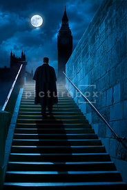 An atmospheric image of a Victorian man in a cloak and stick, walking up some steps at night, in London, England.