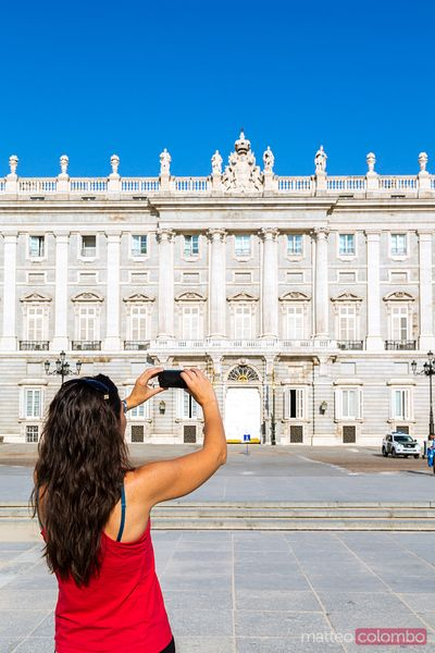 Woman taking a photo of the royal palace, Madrid, Spain