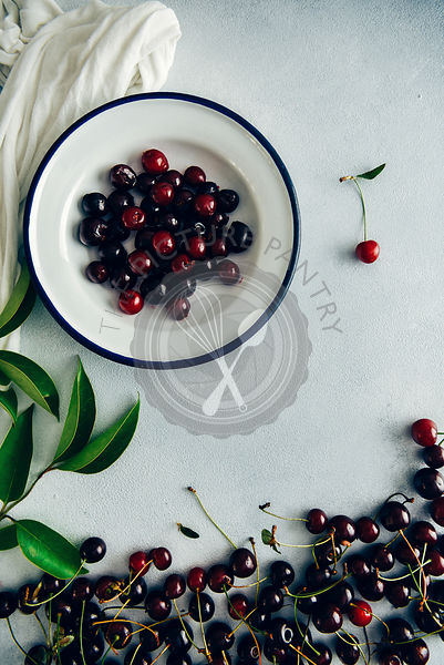 Pitted cherries in a white bowl, whole cherries and green leaves on a grey background photographed from top view.